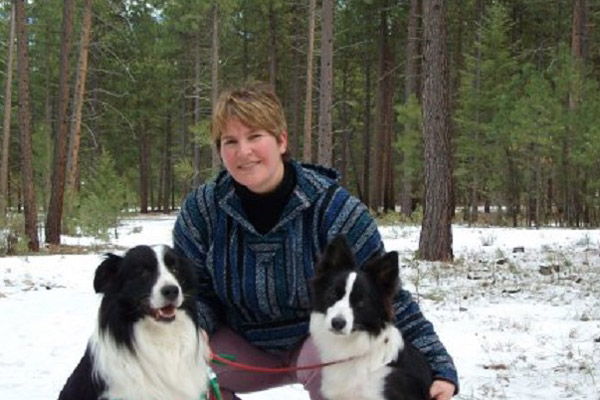 Danette Paige, a short-haired woman, squats in a snowy forest between her two border Collies, whose names are Magic and Chaos.