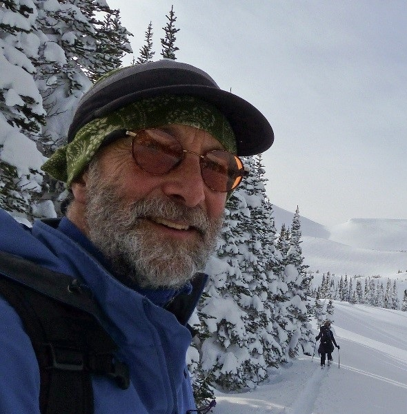Peter smiling in mountaineering gear on a snowy slope. He has a full grey beard.